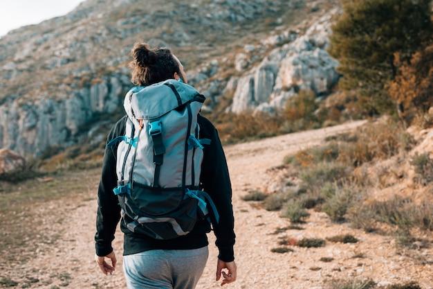Retrovisione di una viandante maschio con lo zaino che fa un'escursione nelle montagne