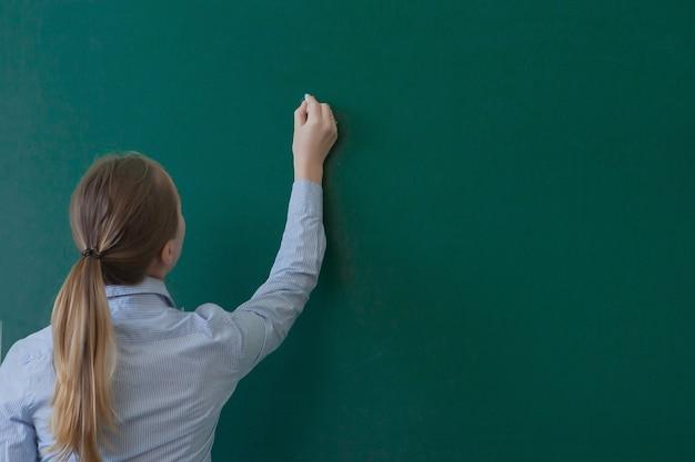 Retrovisione di uno studente o di un insegnante con scrittura lunga dei capelli del brunette su una lavagna o lavagna verde in bianco con copyspace