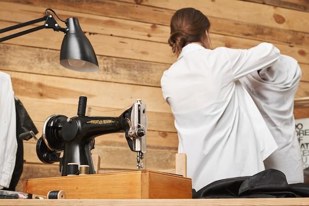 Retrovisore dell'affollata designer di successo del manichino da vestiario mentre lavora in officina per vestire nuovi per il suo negozio, usando la macchina da cucire. donna con fantasia e passatempo interessante