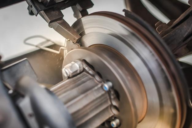 Rettificatrice per dischi freno - tornitrice per freni a disco per veicoli. riparazione del sistema di freno a disco dell'automobile in garage.