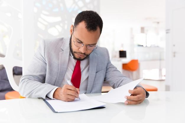 Revisore contabile focalizzato che controlla documento