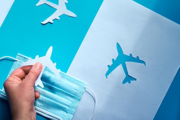 Riavvia il volo, termina la quarantena. la mano che tiene l'aereo di carta sopra la maschera facciale lo prende dall'ombra alla luce. il viaggio aereo riprende dopo il viaggio. pandemie.