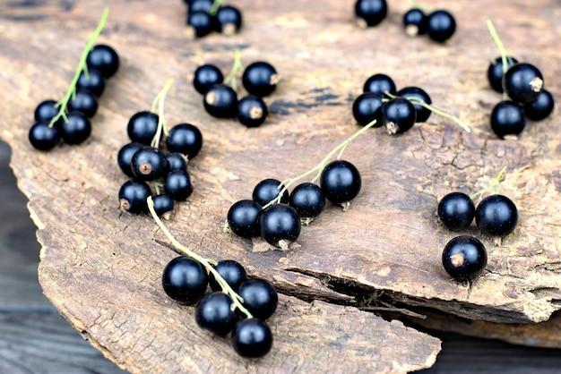 Ribes nero maturo fresco su un vecchio fondo di legno.