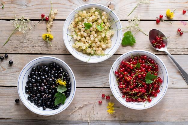 Ribes rosso, bianco e nero in ciotole sulla tavola di legno