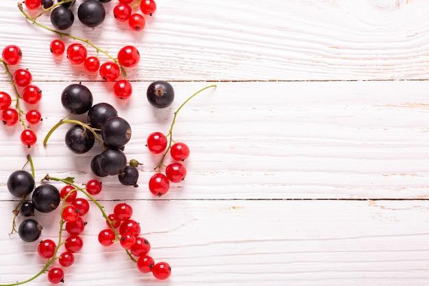 Ribes rosso e nero fresco su un fondo di legno bianco vista dall'alto