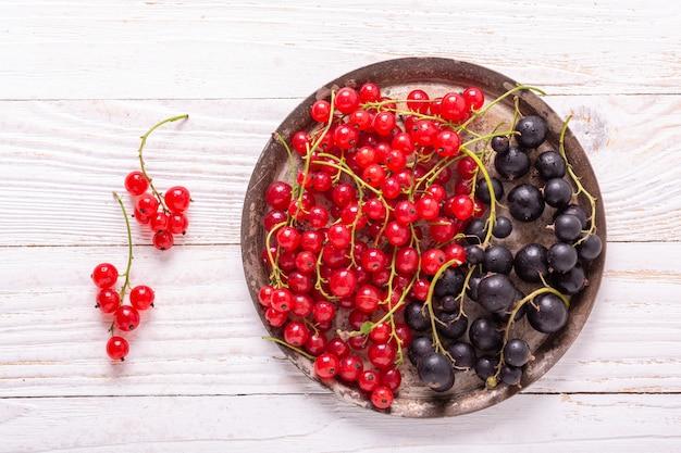 Ribes rosso e nero fresco sulla placca di metallo dell'annata su un fondo di legno bianco vista superiore