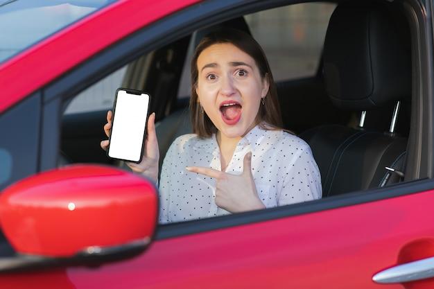 Ricarica auto elettrica e guardando app sul cellulare. primo piano dello schermo dello smartphone. mano che tiene dispositivo intelligente con display bianco. applicazione mobile per il trasporto ecologico