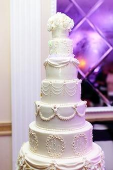 Ricca torta nuziale stanca decorata con iniziali di sposi novelli
