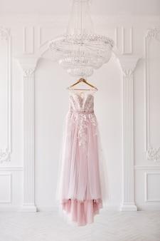 Ricco abito da sposa rosa appeso a un lampadario in una stanza bianca