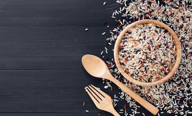 Riceberry organico, riso rosso del gelsomino e riso sbramato (riso di hommali) con il cucchiaio di legno su fondo di legno nero