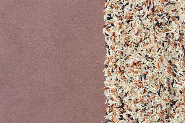 Riceberry organico, riso rosso del gelsomino e riso sbramato (riso di hommali) su fondo di legno
