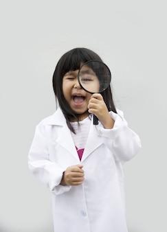 Ricerca asiatica del bambino con il vetro di ingrandimento