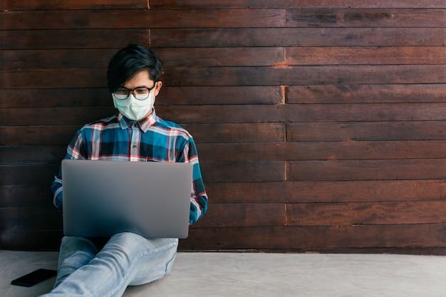 Ricerca di lavoro da uomo asiatico su internet, uomo a casa in cerca di buona carriera, concetto di crisi economica, disoccupazione e produzione delle persone, allo scoppio della malattia di coronavirus 2019 o covid-19.