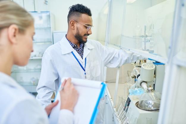 Ricercatore allegro e il suo assistente che utilizzano attrezzature di laboratorio