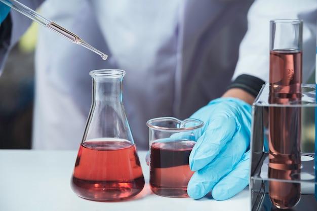 Ricercatore con provette chimiche da laboratorio in vetro con liquido per analisi, medico
