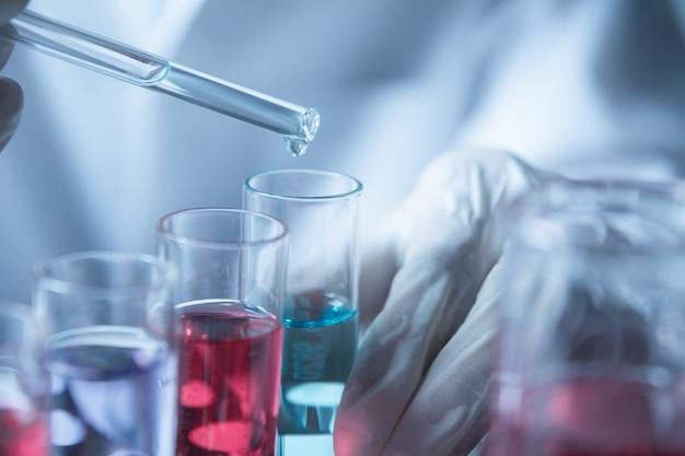 Ricercatore con provette chimiche da laboratorio in vetro con liquido