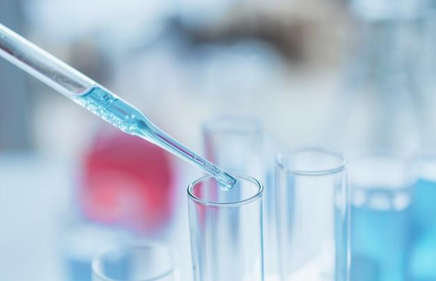 Ricercatore con provette chimiche di vetro da laboratorio con liquido per concetto di ricerca analitica, medica, farmaceutica e scientifica.