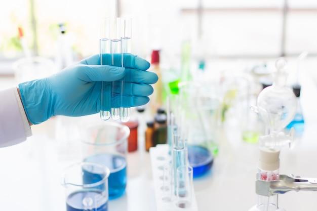 Ricercatori e scienziati che indossano guanti di gomma trasportano provette contenenti sostanze chimiche in un laboratorio.