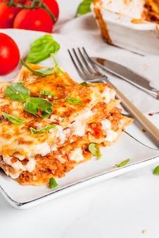 Ricetta del cibo italiano. cena con lasagne classiche alla bolognese con salsa besciamella, parmigiano, basilico e pomodori