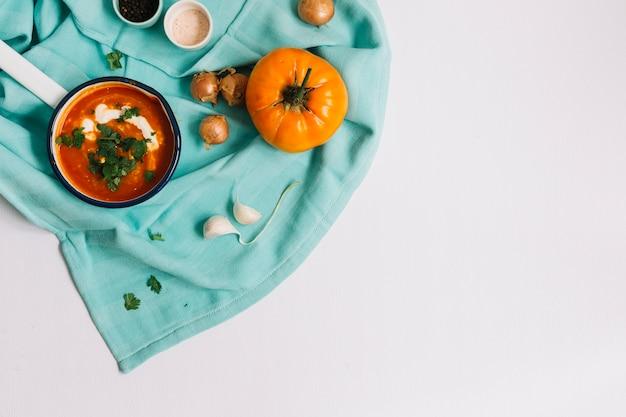 Ricetta del pomodoro di cimelio in casseruola sul tovagliolo blu contro fondo bianco