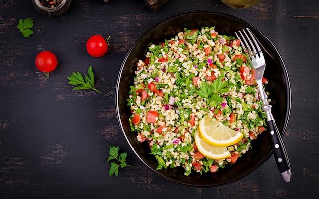Ricetta mediorientale di verdure e grano tipo cous cous. piatto tradizionale mediorientale o arabo. insalata vegetariana levantina con prezzemolo, menta, bulgur, pomodoro.