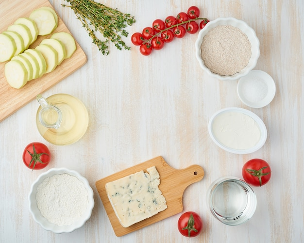 Ricetta passo dopo passo galette fatta in casa con verdure. vista dall'alto, tavolo in legno bianco
