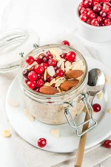 Ricetta per una sana colazione invernale, idee per la mattina di natale. farina d'avena durante la notte con mandorle, mirtilli rossi, zucchero. . copyspace