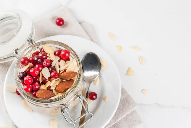 Ricetta per una sana colazione invernale, idee per la mattina di natale. farina d'avena durante la notte con mandorle, mirtilli rossi, zucchero. su un tavolo di marmo bianco. vista dall'alto