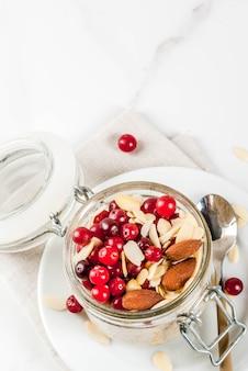 Ricetta per una sana colazione invernale, idee per la mattina di natale. farina d'avena durante la notte con mandorle, mirtilli rossi, zucchero.