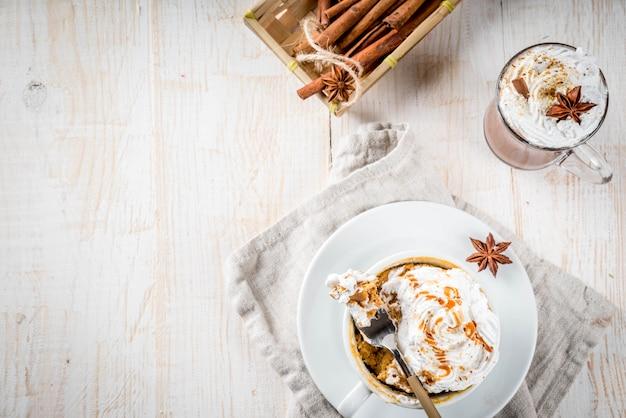 Ricette con zucche, fast food, farina a microonde. torta di zucca piccante in tazza, con panna montata, gelato, cannella, anice. sul tavolo di legno bianco, con una tazza di cioccolata calda. vista dall'alto di copyspace