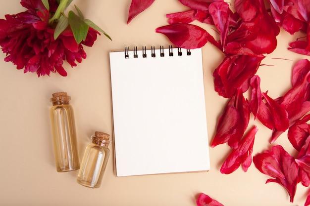 Ricette concetto di bellezza. taccuino, bottiglie di essenza, petali di fiori distesi con spazio di copia