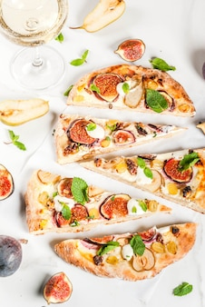 Ricette da forno autunnali. pizza dolce focaccia o focaccia di frutta con fichi, pere, uva, crema di formaggio, noci e menta