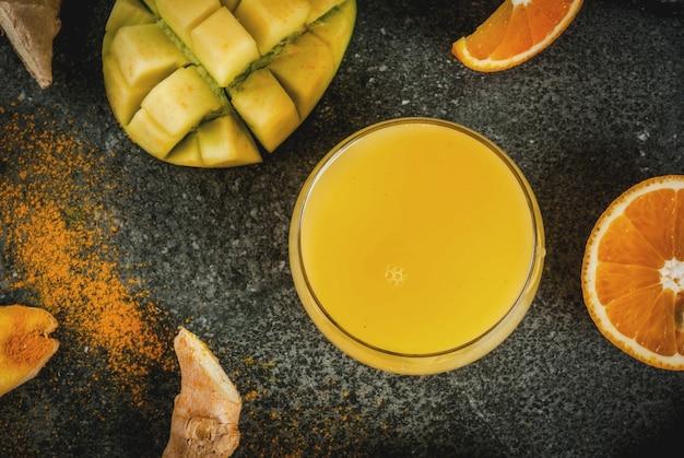 Ricette della cucina indiana. cibo sano, acqua disintossicante. frullato tradizionale indiano di mango, arancia, curcuma e zenzero, su un tavolo di pietra scura. vista dall'alto