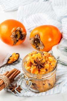 Ricette indiane tradizionali dell'alimento chutney della frutta del cachi con fondo di marmo bianco delle stelle dell'anice e della cannella