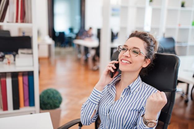 Ricevere buone notizie economiche. bella giovane donna parlando al telefono cellulare