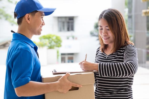 Ricevuta di firma della donna asiatica del pacchetto consegnato