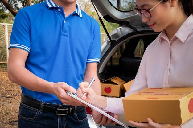 Ricevuta di firma della donna su carta dall'uomo di consegna per ottenere il suo pacchetto, concetto di consegna