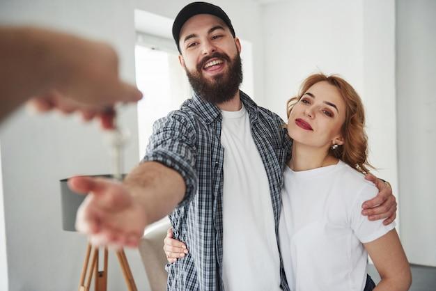Ricezione delle chiavi. coppia felice insieme nella loro nuova casa. concezione del movimento