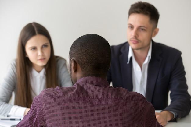 Richiedente africano che parla rispondendo domanda al colloquio di lavoro, retrovisione