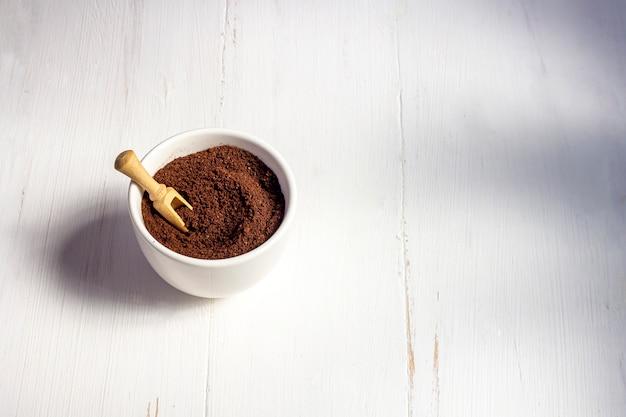 Riciclaggio dei rifiuti dal caffè. il corpo sfrega il caffè macinato, il cosmetico fatto in casa per la sbucciatura e la cura della stazione termale su fondo bianco.