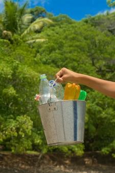 Riciclare, cestino con bottiglia di plastica in spiaggia