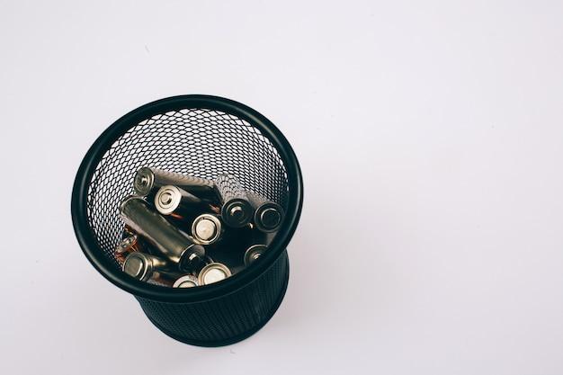 Riciclare, riutilizzare, ridurre il concetto. proteggi un ambiente. batterie d'argento monouso nella scatola di metallo su whitewall, vista dall'alto. rifiuti elettrici monouso