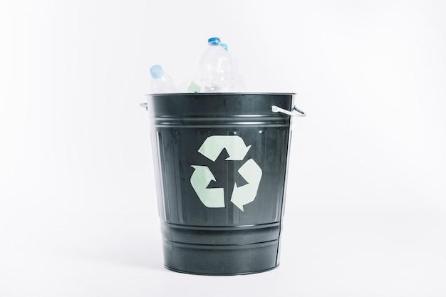 Ricicli il secchio con le bottiglie di plastica su fondo bianco