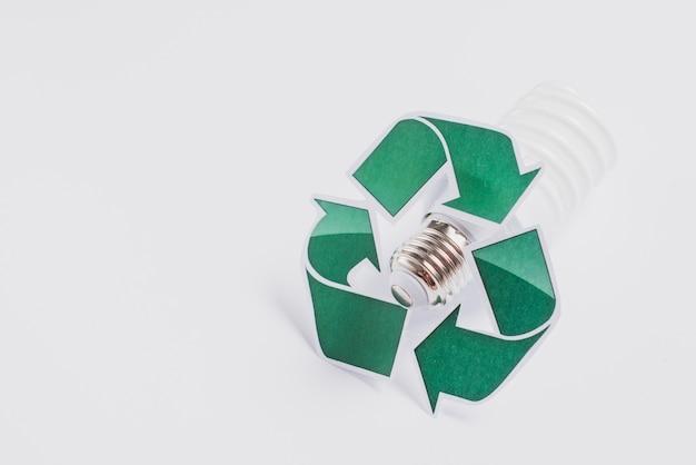 Ricicli il simbolo sulla lampadina fluorescente compatta isolata su fondo bianco