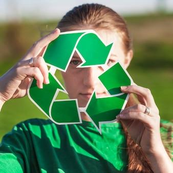 Ricicli la priorità bassa con la holding della donna ricicli il segno