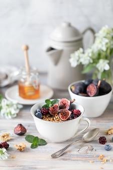 Ricotta con fichi, bacche, miele. tazza di caffè e caffettiera. prima colazione. tavolo di legno.
