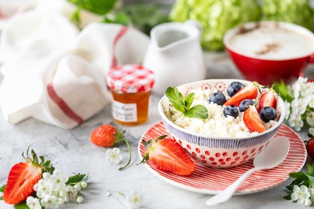 Ricotta con frutti di bosco, marmellata, fragole fresche e una tazza di caffè con panna per colazione.