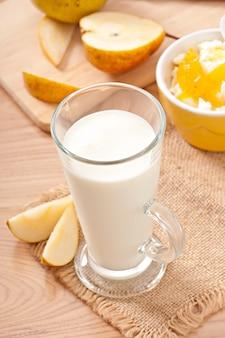 Ricotta con marmellata di pere in una ciotola e un bicchiere di latte