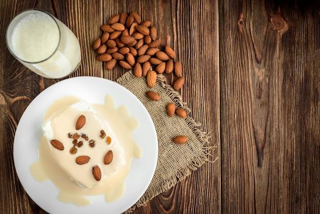 Ricotta con yogurt e mandorle su legno scuro.
