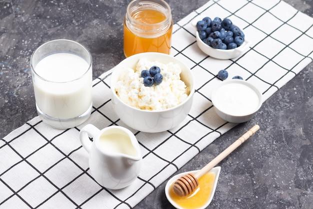 Ricotta di grano in una ciotola bianca con una brocca di latte su uno sfondo chiaro